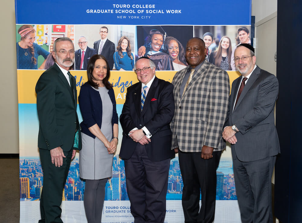 During Touro\'s Graduate School of Social Work\'s Community Day on March 13, students and faculty members listened to speeches about resilience from speakers (left to right): David Mandel, CEO of Ohel Children's Home and Family Services, GSSW\'s Dr. Annecy Baez, GSSW Dean Steven Huberman, Ph.D., GSSW alumnus Bobby Staley, and Touro Executive Vice President Rabbi Moshe Krupka.